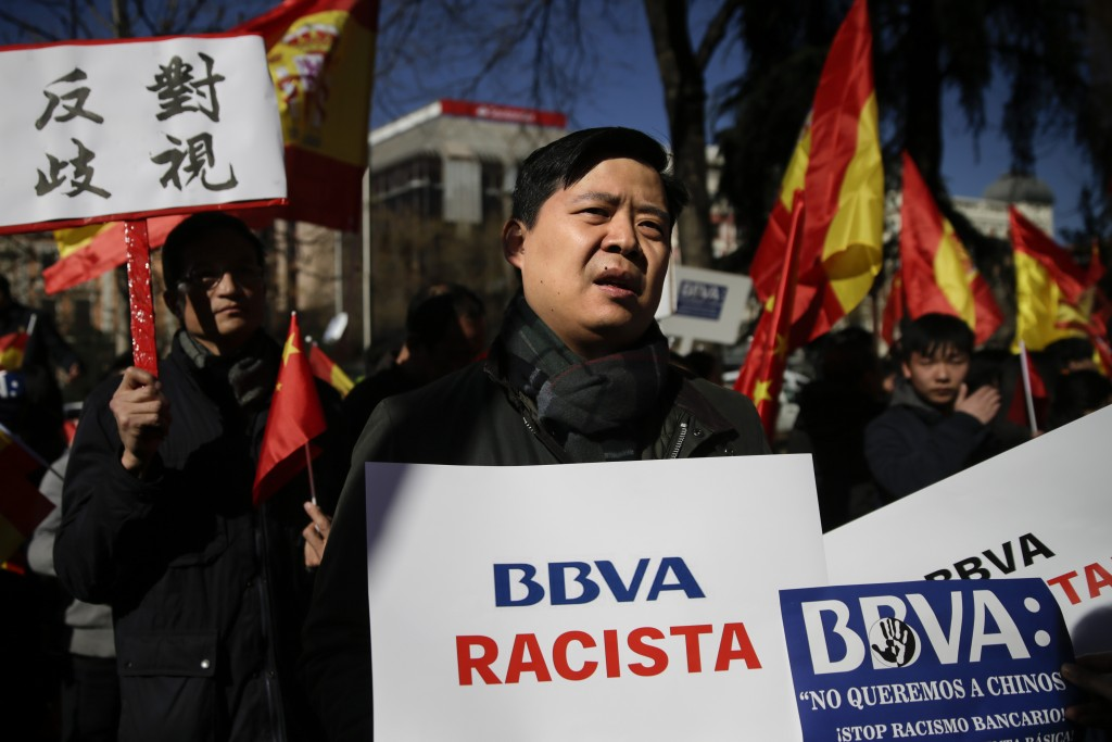"""A man protests holding a banner reading in Spanish """"BBVA racist"""" outside a BBVA bank building in Madrid, Spain, Friday, Feb. 15. 2019.  Hundreds of Ch..."""