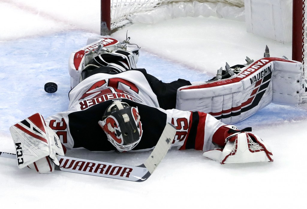 New Jersey Devils goalie Cory Schneider cannot stop a goal by Chicago Blackhawks center Jonathan Toews during the second period of an NHL hockey game ...