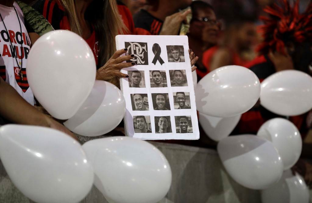 A woman holds a poster composed with images of the 10 teenage players killed by a fire at the Flamengo training center last Friday, at the Maracana St...