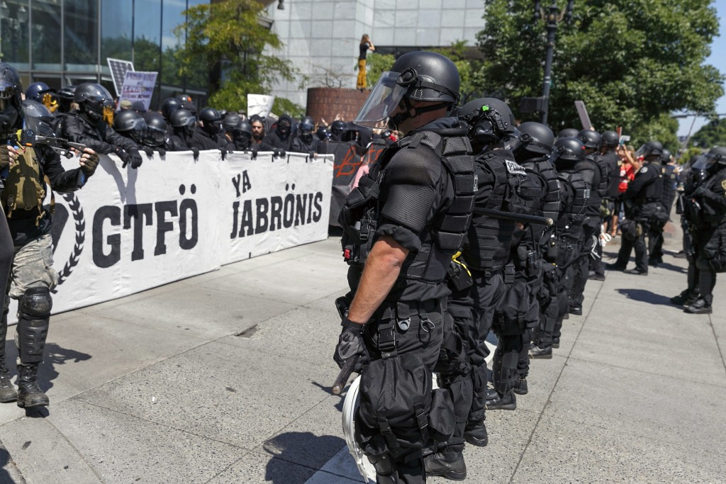 FILE - In this Aug. 4, 2018, file photo, Portland police keep Patriot Prayer affiliates separate from antifa protesters during a rally in Portland, Or...