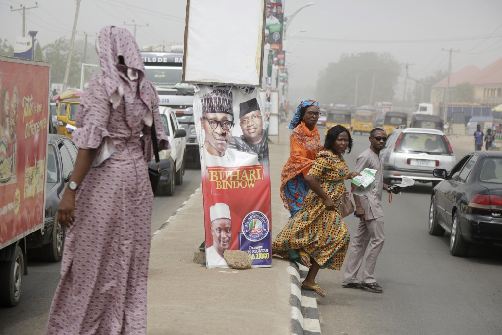 People cross the roads near the Independent National Electoral Commission office in Yola, Nigeria, Friday, Feb. 15, 2019. Nigeria's main opposition pa...