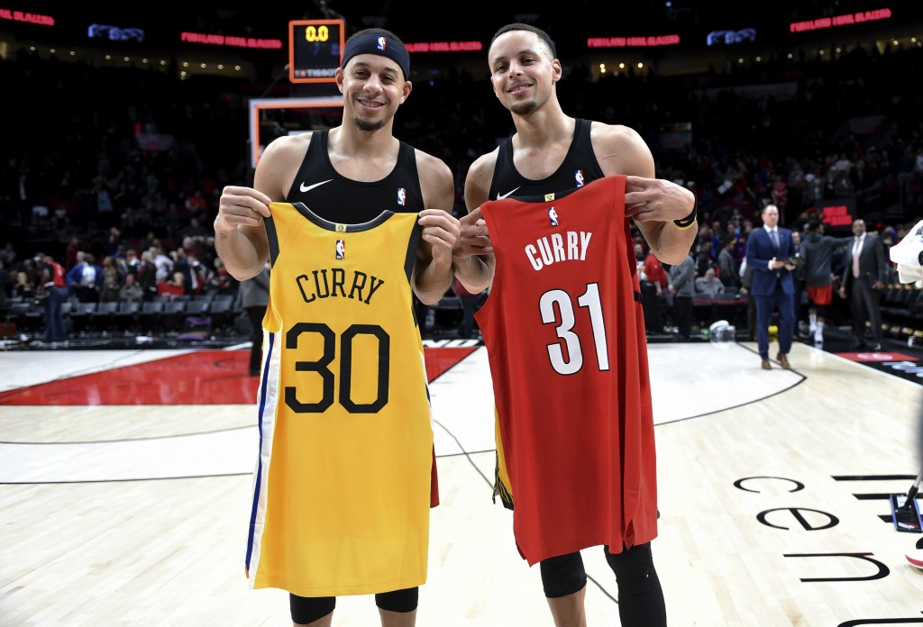 FILE - In this Dec. 29, 2018, file photo, Portland Trail Blazers guard Seth Curry, left, and his brother, Golden State Warriors guard Stephen Curry, e...