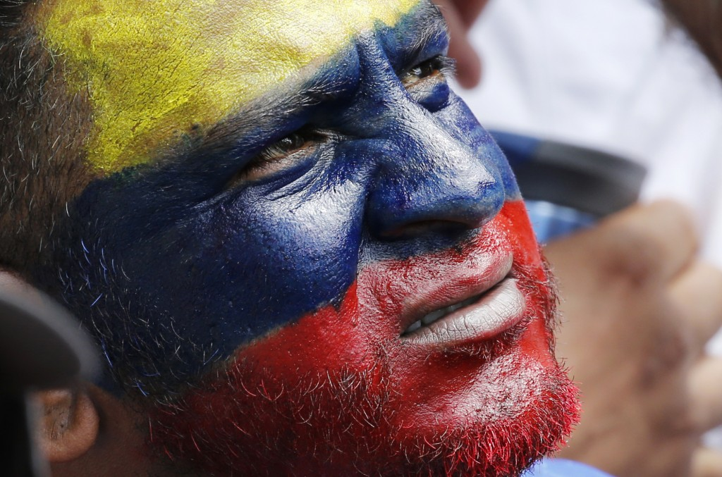 In this Feb. 12, 2019 photo, a man, his face painted with the colors of the Venezuelan national flag, listens to opposition leader and self-proclaimed...