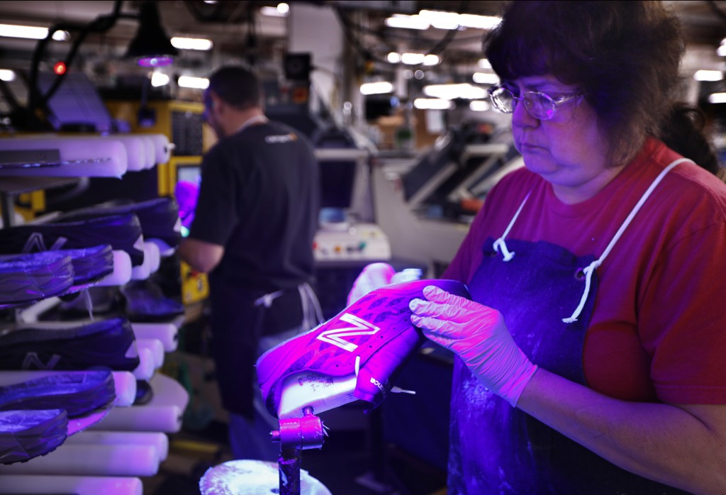 FILE- In this Dec. 17, 2018 photo, Laurie French applies adhesive under an ultraviolet light to a pair of athletic shoes designed for the military at ...