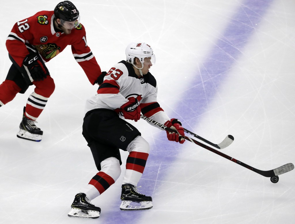 New Jersey Devils left wing Jesper Bratt, right, controls the puck against Chicago Blackhawks left wing Alex DeBrincat during the first period of an N...