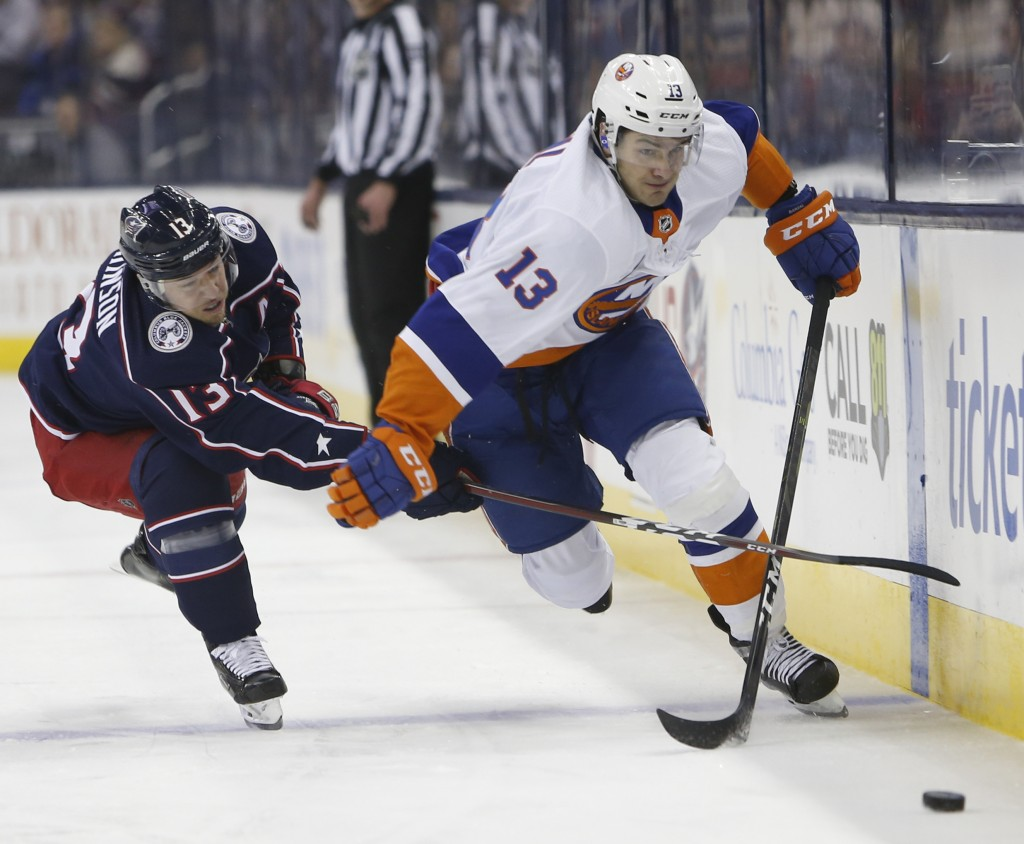 New York Islanders' Mathew Barzal, right, carries the puck across the blur line as Columbus Blue Jackets' Cam Atkinson defends during the first period...