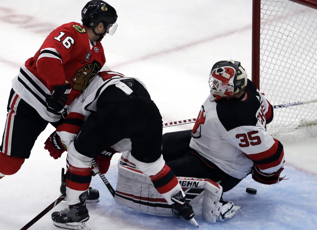 New Jersey Devils goalie Cory Schneider, right, tries to stop a shot by Chicago Blackhawks center Marcus Kruger (16) during the second period of an NH...