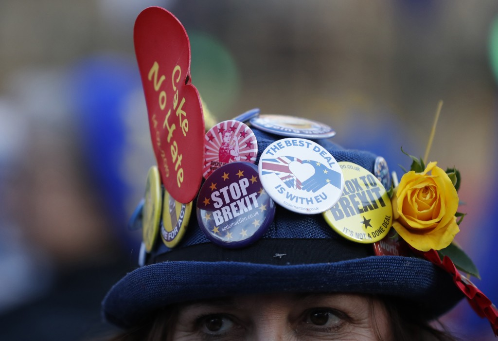 An anti-Brexit demonstrator wears a hat adorned with anti Brexit statements as she protests outside the Palace of Westminster in London, Thursday, Feb...