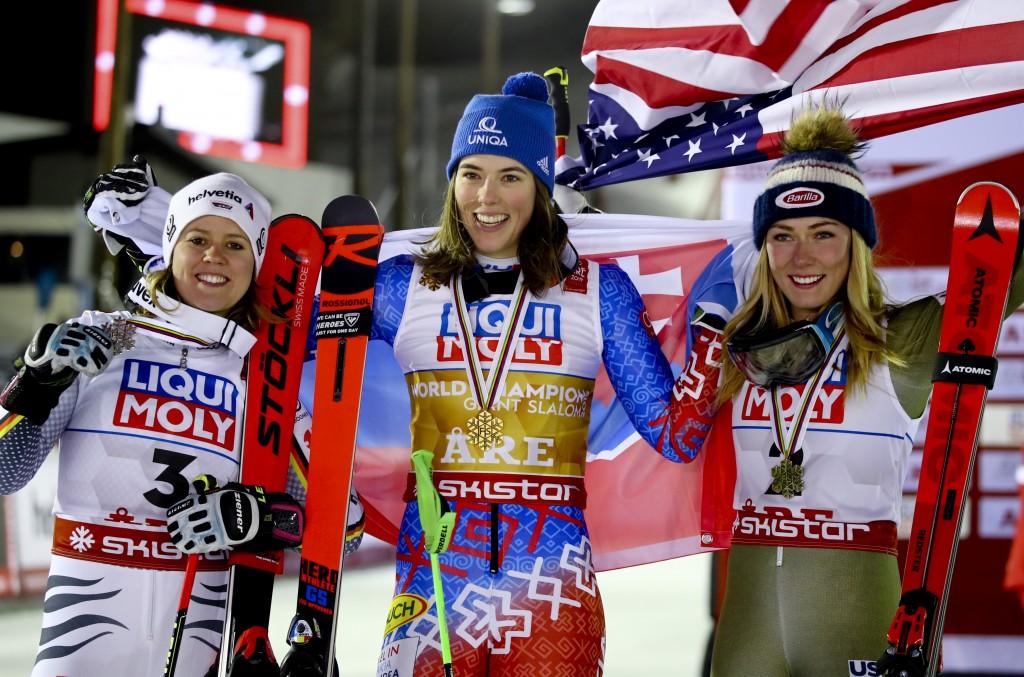 Slovakia's Petra Vlhova, center, shows her gold medal of the women's giant slalom, flanked by silver medal's winner Germany's Viktoria Rebensburg, lef...