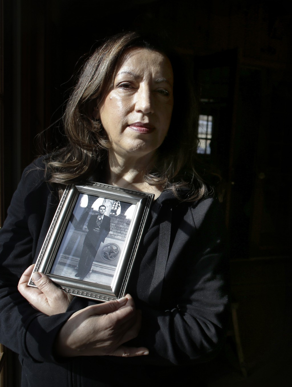 In this Sunday, Feb. 10, 2019 photo Christina Lamb, daughter of California wildfire victim Julian Binstock, holds a 1950s photo of her father at her h...