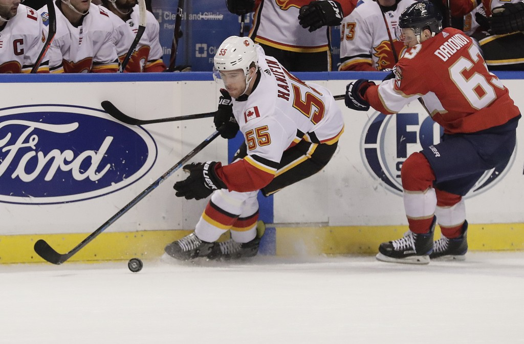 Calgary Flames defenseman Noah Hanifin battles for the puck with Florida Panthers right wing Evgenii Dadonov during the first period of an NHL hockey ...