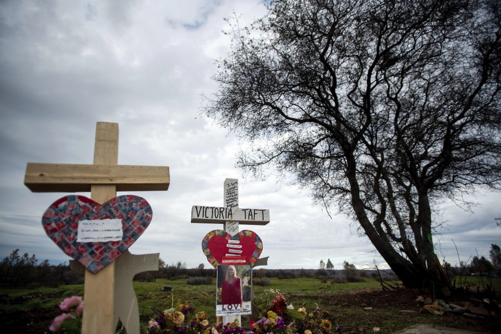In this Feb. 8, 2019, photo, a cross for Victoria Taft, right, stands at a memorial for Camp Fire victims in Paradise, Calif. In the 100 days since a ...