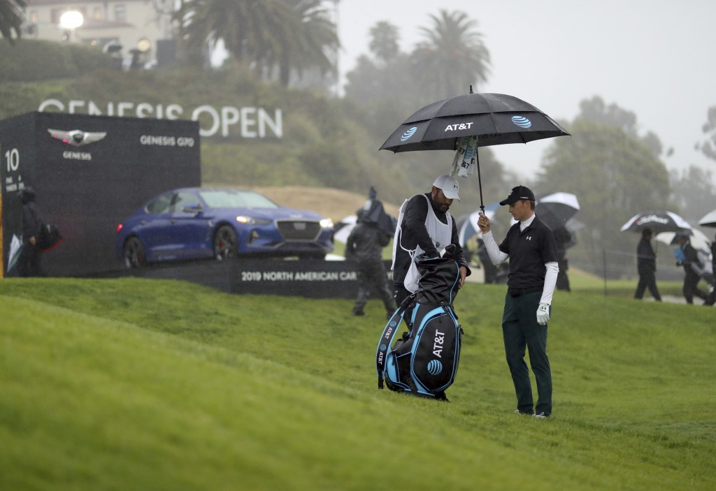 Jordan Spieth holds an umbrella for his caddie, Michael Greller, on the 10th hole before play was suspended during the first round of the Genesis Open...