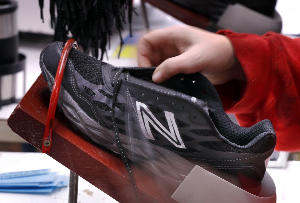 FILE- In this Dec. 17, 2018, file photo, a pair of athletic shoes designed for the military are laced up at a New Balance factory in Norridgewock, Mai...
