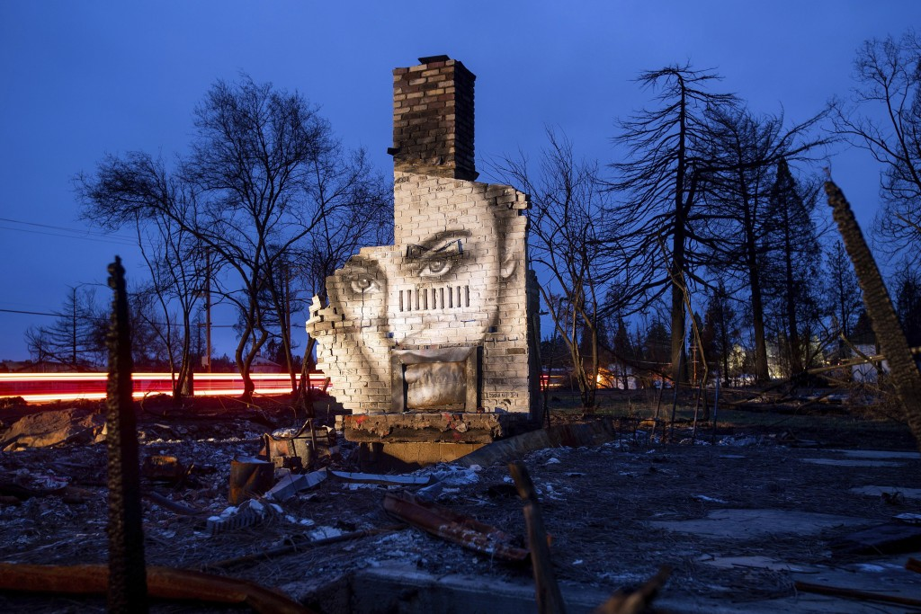 In this Feb. 8, 2019, photo, a mural by artist Shane Grammer adorns the chimney of a residence leveled by the Camp Fire in Paradise, Calif. Grammer sa...