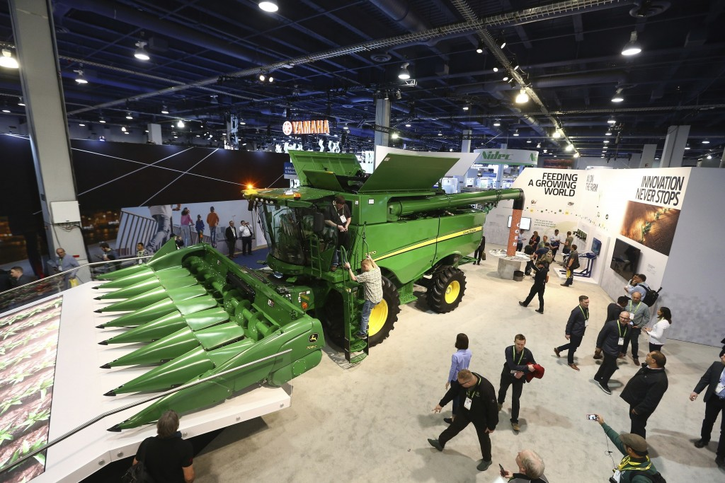 FILE- In this Jan. 8, 2019, file photo a John Deere combine harvester is displayed at CES International in Las Vegas. Deere & Co. reports earns on Fri...
