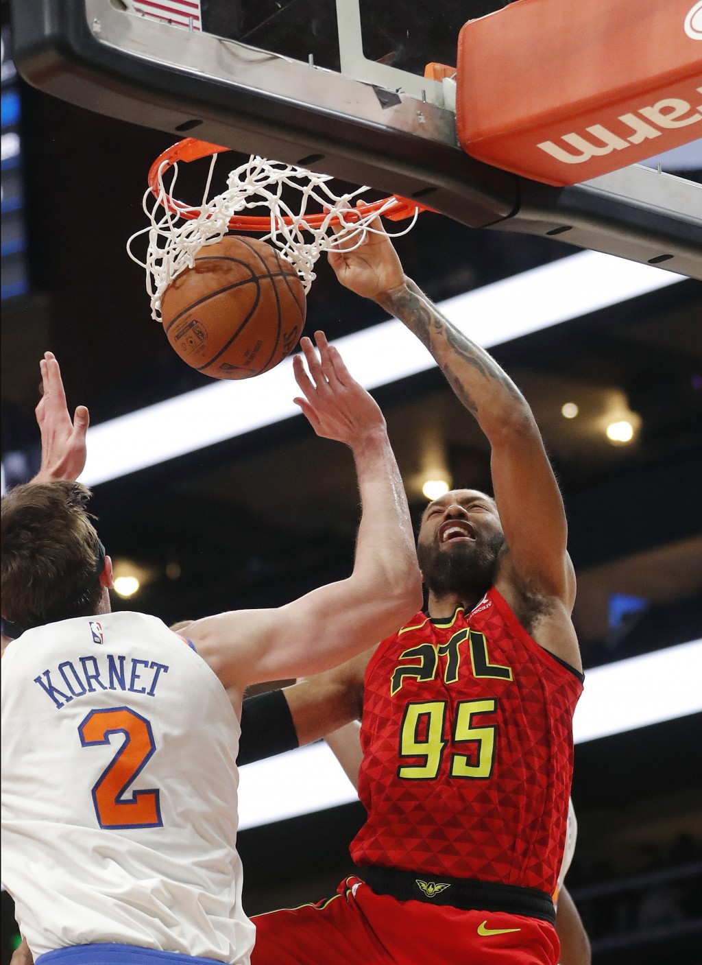 Atlanta Hawks forward DeAndre' Bembry (95) scores as New York Knicks forward Luke Kornet (2) defends during the first half of an NBA basketball game T...