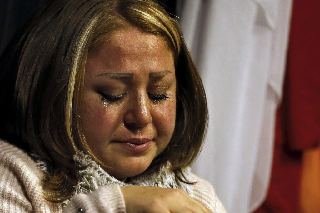 In this Friday, Feb. 8, 2019 photo, a Syrian woman who identified herself as Mae weeps as she speaks about her brother who was kidnapped in 2013 and h...
