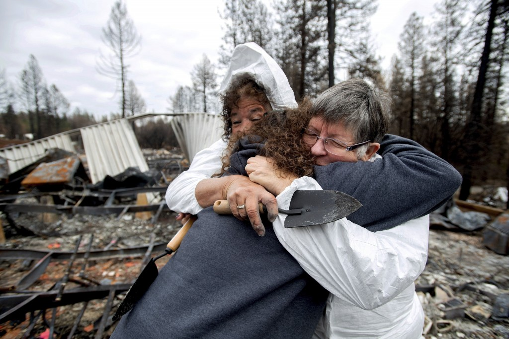In this Feb. 8, 2019, photo, Carol Beall, right, hugs friends as they comb through the remains of her residence, destroyed by the Camp Fire, in Paradi...