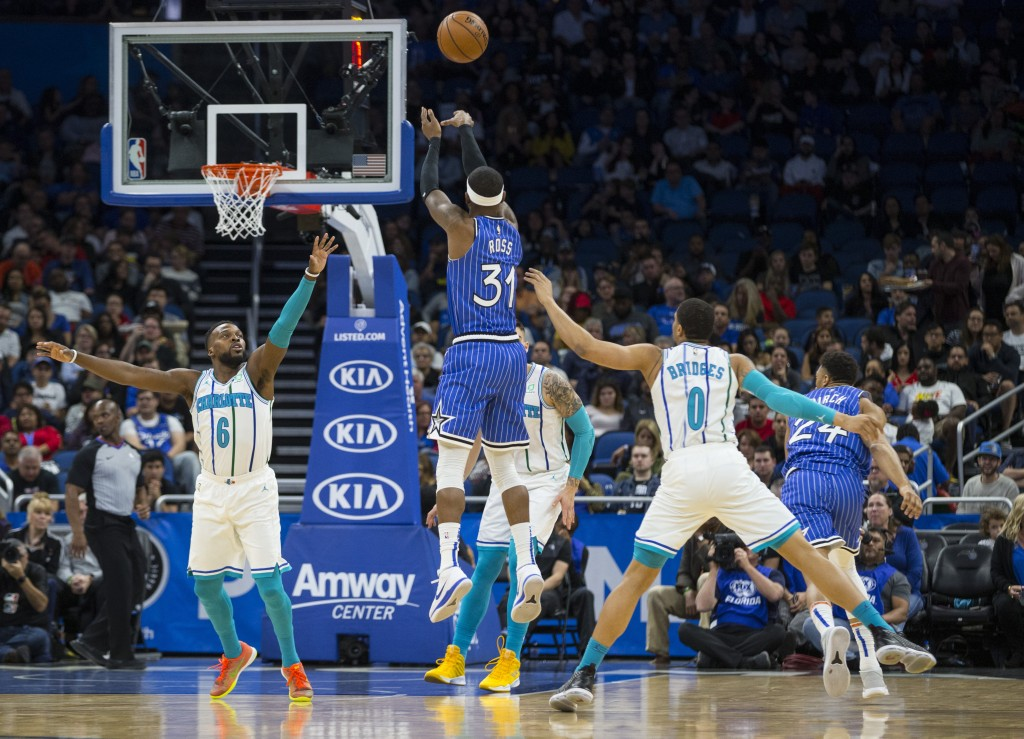 Orlando Magic guard Terrence Ross (31) scores against Charlotte Hornets guard Shelvin Mack (6) and forward Miles Bridges (0) during the first half of ...