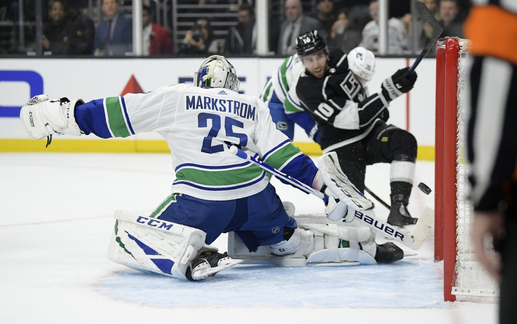 Los Angeles Kings center Michael Amadio, right, scores on Vancouver Canucks goaltender Jacob Markstrom during the second period of an NHL hockey game ...