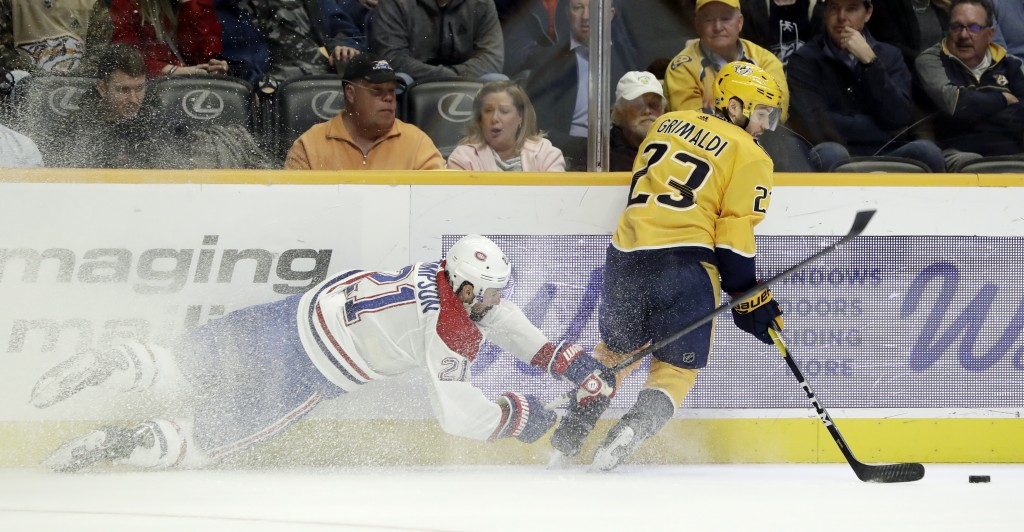 Montreal Canadiens center Nate Thompson (21) tries to slow down Nashville Predators center Rocco Grimaldi (23) in the first period of an NHL hockey ga...