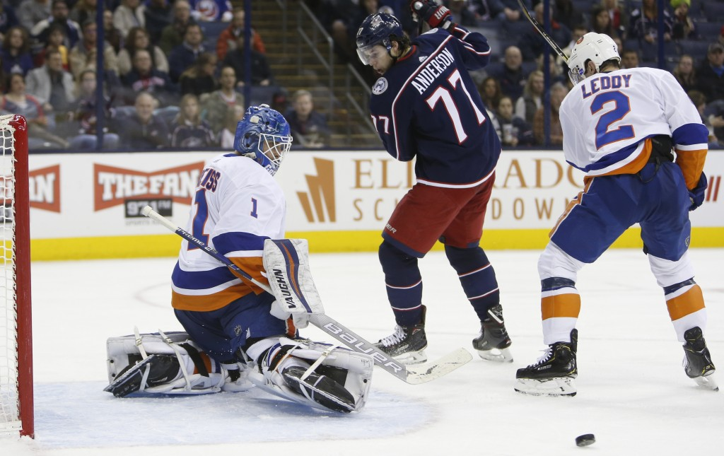 New York Islanders' Thomas Greiss, left, of Germany, makes a save as teammate Nick Leddy, right, and Columbus Blue Jackets' Josh Anderson look for the...