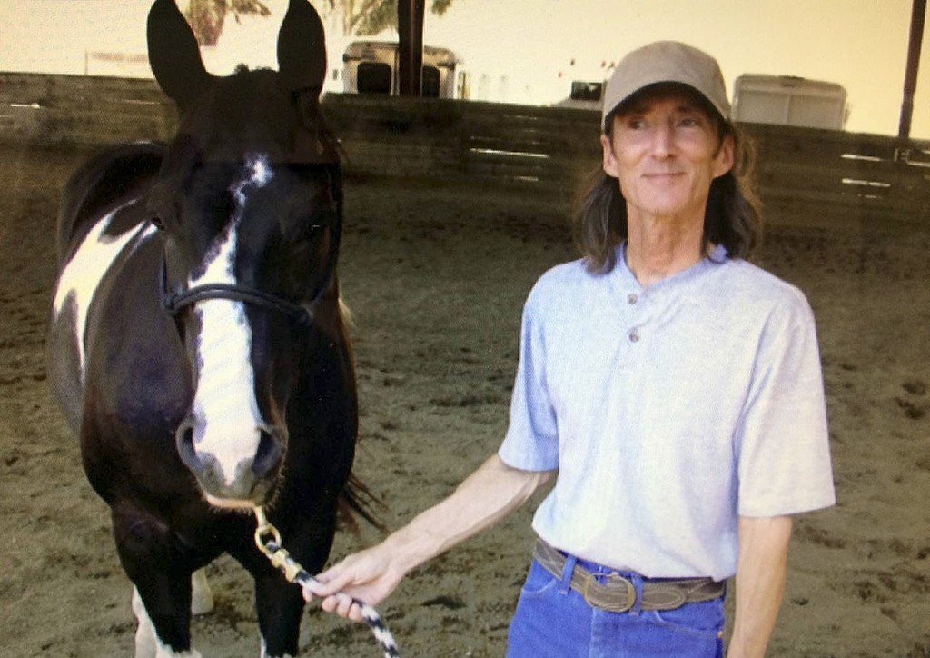 This 2003 photo provided by Mickey Sanders shows David Marbury posing for photos with his horse Slick at Briones Horse Center in Martinez, Calif. A pr...