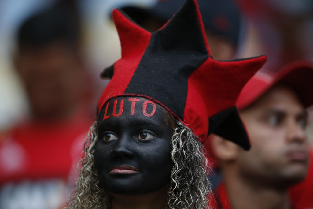 "A woman, with the Portuguese word for ""in mourning"" painted on her forehead, waits for the start of a homage for the 10 teenage   players killed by a ..."