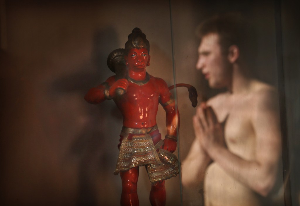 In this Feb. 6, 2019, photo, a player folds his hands in reverence near a statue of Hindu monkey-god Hanuman, a respected deity whose blessings are ev...