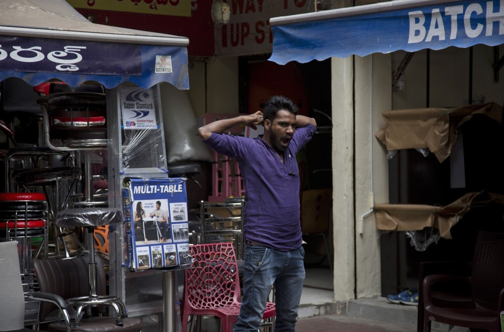 In this Dec. 17, 2018, photo, a salesman yawns while waiting for customers at the Nampally furniture market in Hyderabad, India. This furniture market...