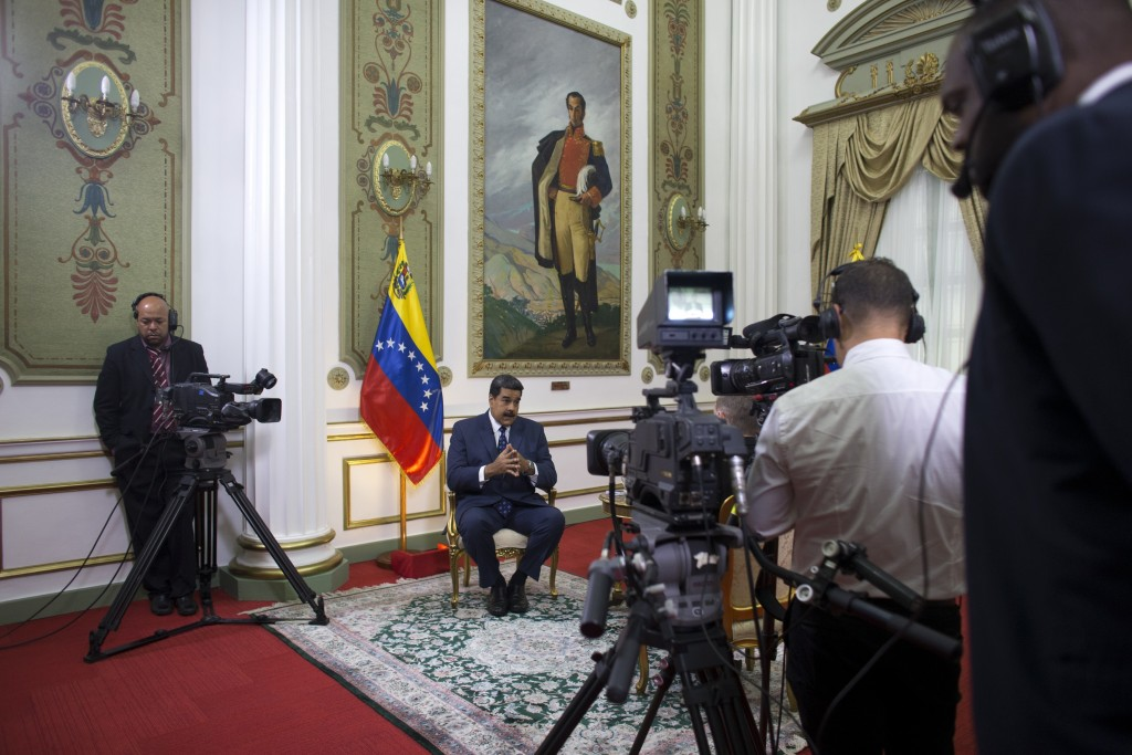 Venezuela's President Nicolas Maduro speaks during an interview with The Associated Press at Miraflores presidential palace, where a painting of indep...