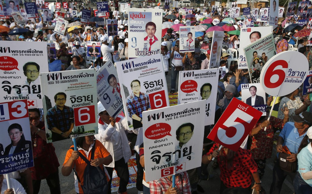 Supporters raise posters of Pheu Thai Party's candidates during an election campaign in Bangkok, Thailand, Friday, Feb. 15, 2019. The nation's first g...