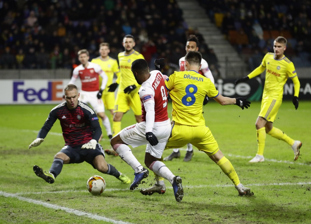 Bate goalkeeper Denis Scherbitski, left, makes a save in front of Arsenal's Alexandre Lacazette, front left, during the Europa League round of 32 firs...
