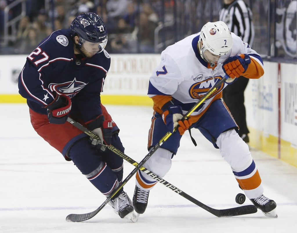 Columbus Blue Jackets' Ryan Murray, left, and New York Islanders' Jordan Eberle fight for the puck during the first period of an NHL hockey game Thurs...
