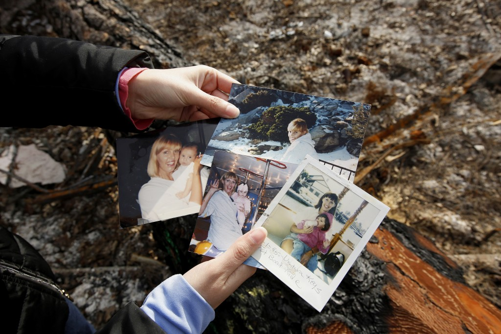 In this Thursday, Feb. 7, 2019 photo, Christina Taft, the daughter of Camp Fire victim Victoria Taft, displays several photos of her mother at the bur...