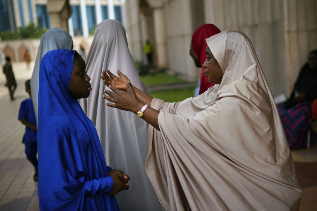 A Nigerian woman attends Friday prayers at the central mosque is security checked a day prior to the election, in Abuja, Nigeria, Friday Feb. 15, 2019...