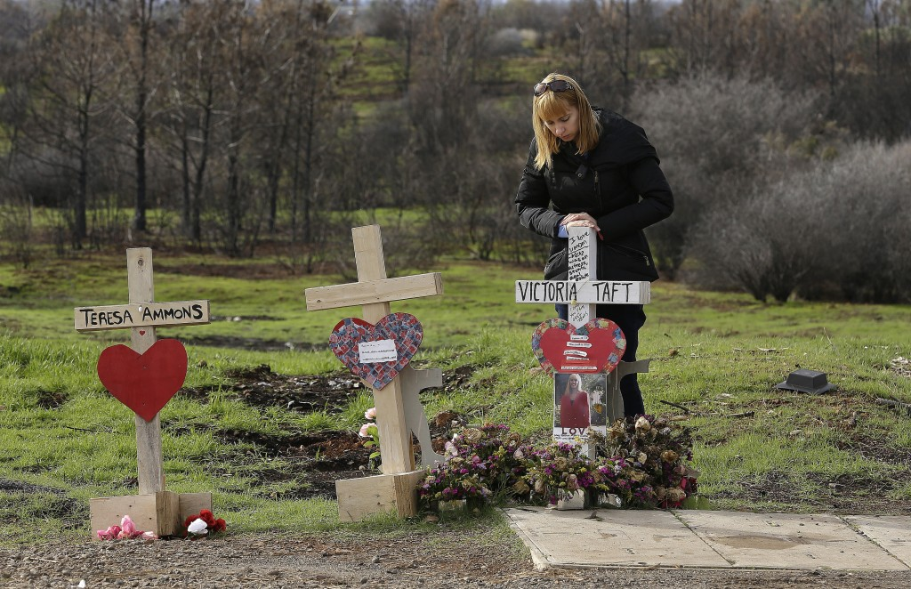 In this Thursday, Feb. 7, 2019 photo, Christina Taft, the daughter of Camp Fire victim Victoria Taft, pauses at a cross bearing her mothers name at a ...