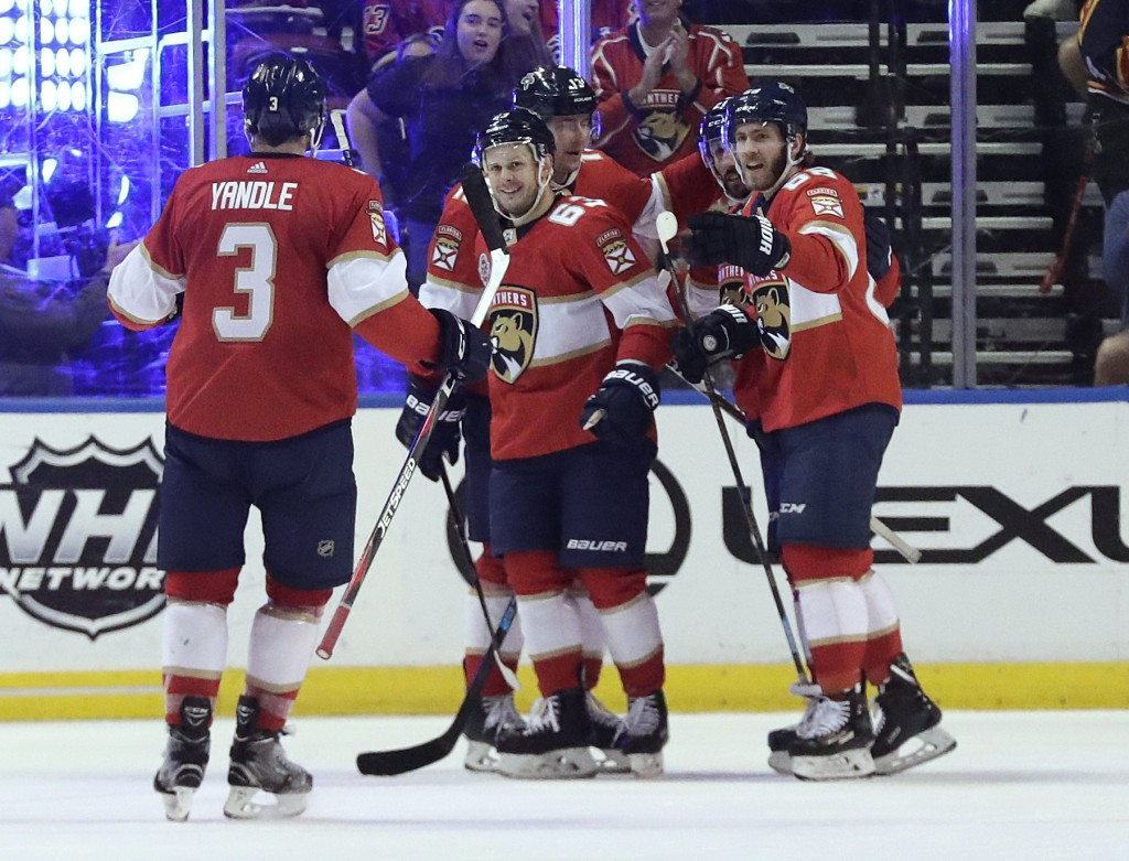 Florida Panthers right wing Evgenii Dadonov, center, celebrates with teammates after scoring during the second period of an NHL hockey game against th...