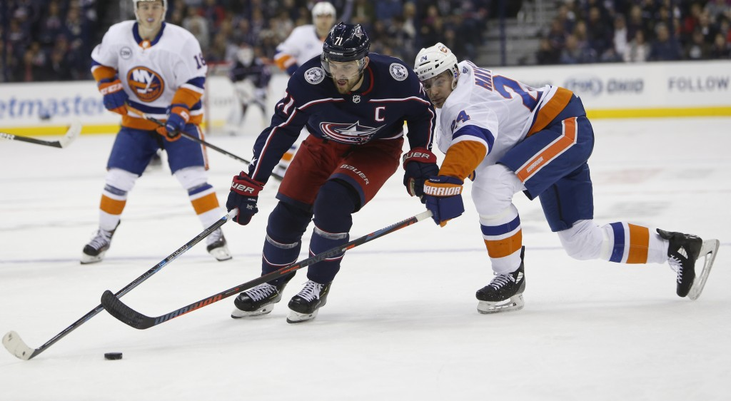 Columbus Blue Jackets' Nick Foligno, left, carries the puck upice as New York Islanders' Scott Mayfield defends during the second period of an NHL hoc...