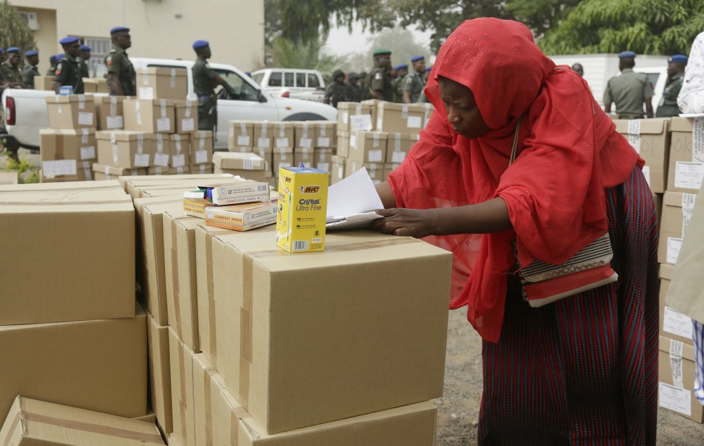 An electoral worker takes stock of ballot papers to be transporters at the offices of the Independent National Electoral Commission in Yola, Nigeria, ...