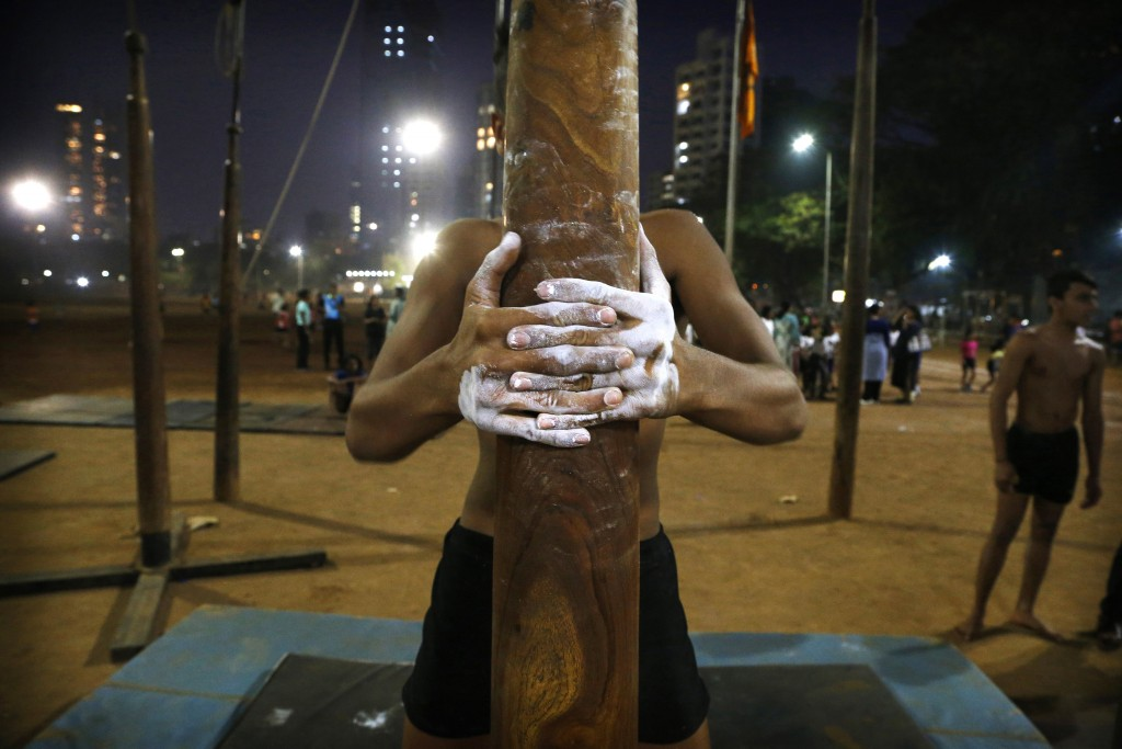 In this Feb. 4, 2019, photo, a player tightens his grip on a mallakhamb pole as he trains at Shivaji Park in Mumbai, India. The word mallakhamb comes ...