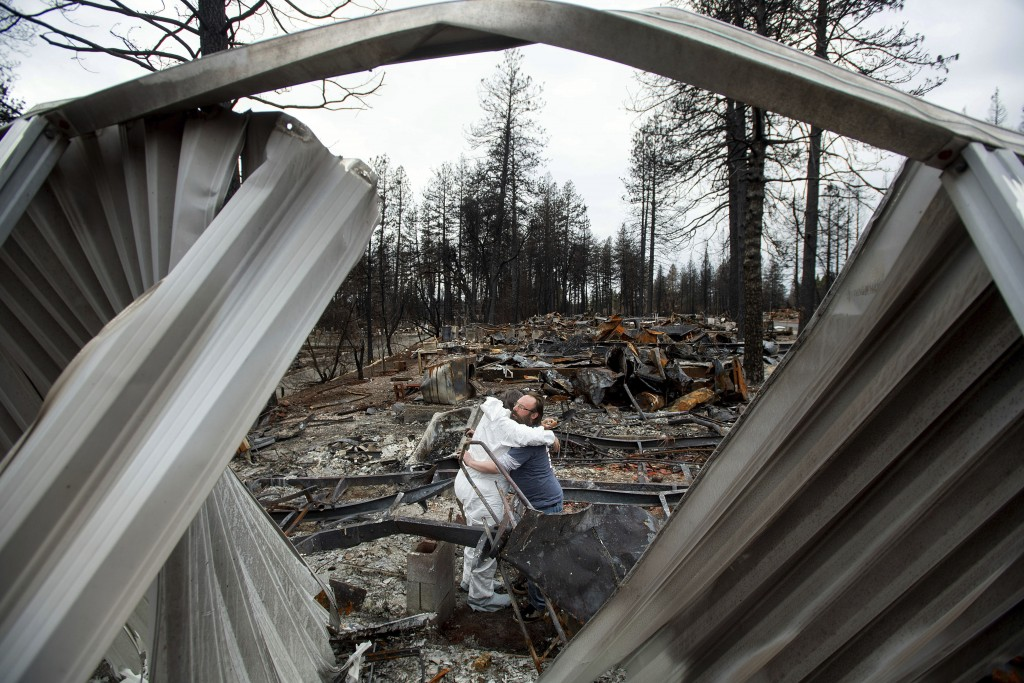 In this Feb. 8, 2019, photo, Bud Daneau hugs Carol Beall while helping her comb through her residence, destroyed by the Camp Fire, at the Ridgewood Mo...