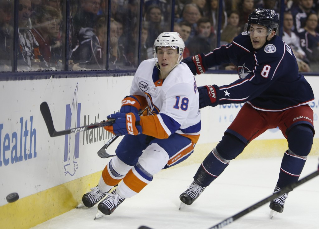 New York Islanders' Anthony Beauvillier, left, passes the puck as Columbus Blue Jackets' Zach Werenski defends during the first period of an NHL hocke...