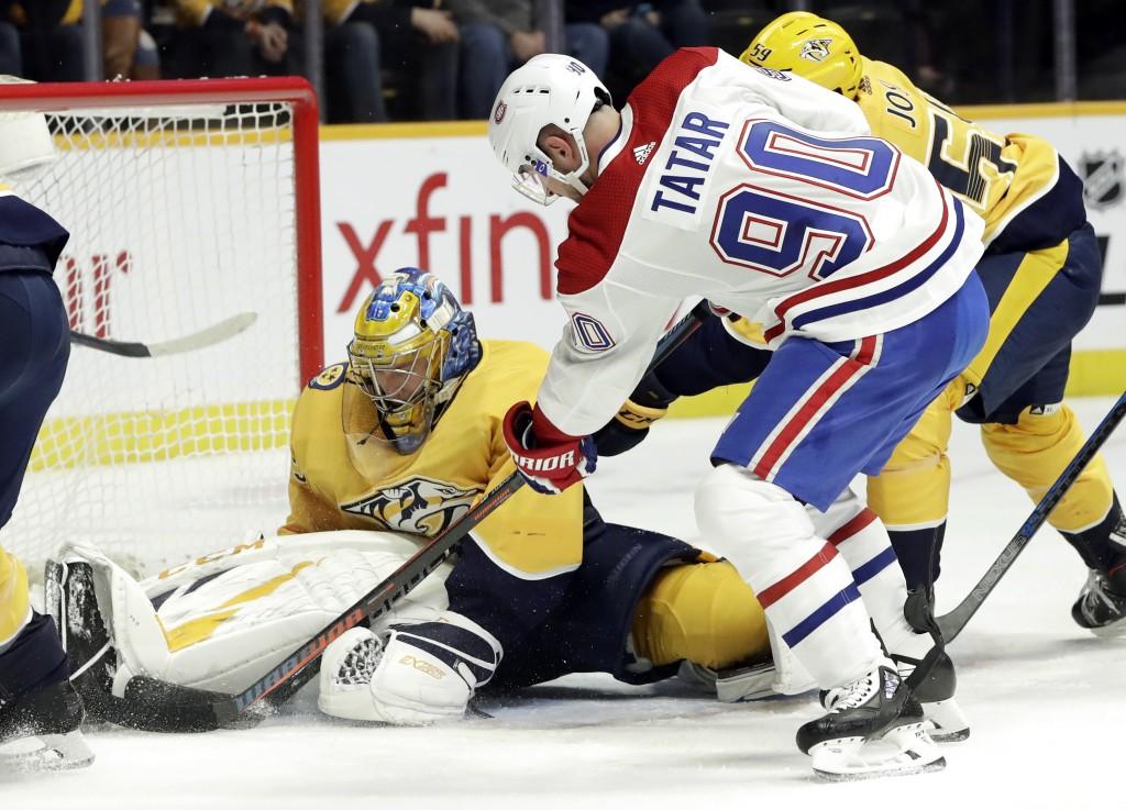 Nashville Predators goaltender Pekka Rinne, of Finland, blocks a shot as Montreal Canadiens left wing Tomas Tatar, of Slovakia, reaches for the reboun...