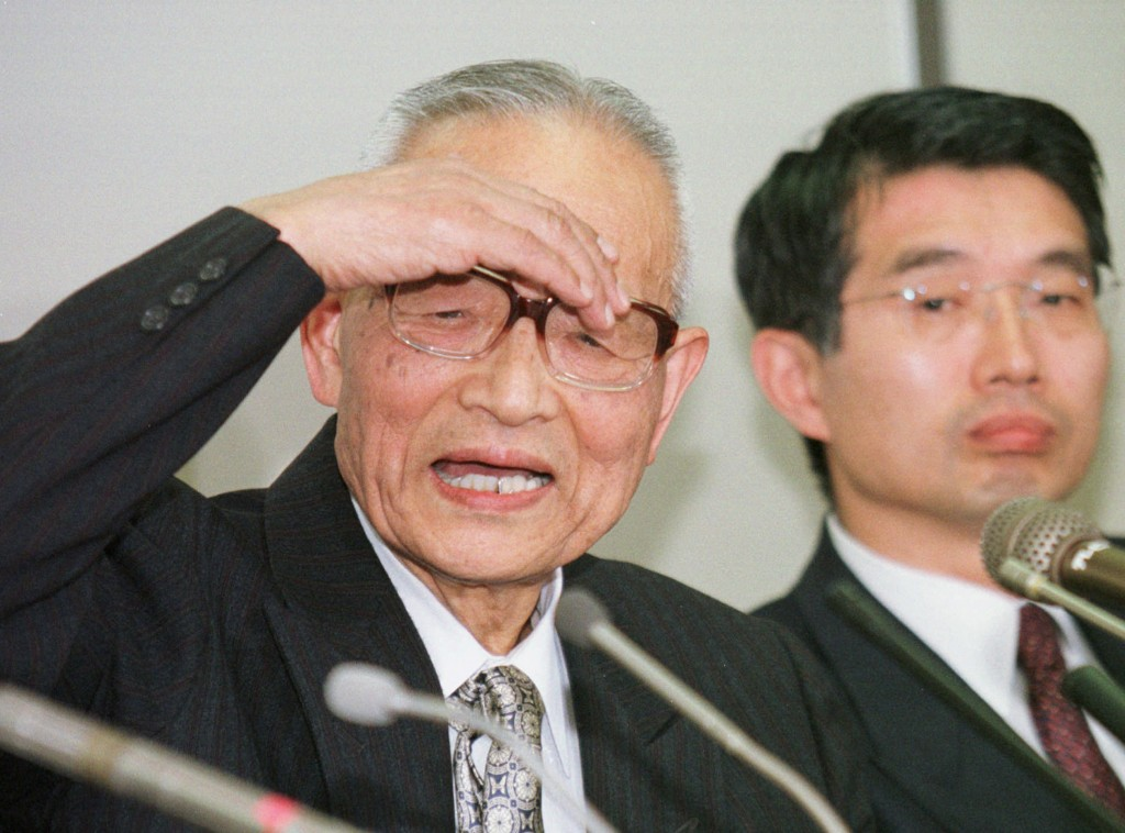 FILE - In this March 10, 1997, file photo, Takeshi Abe, left, a professor and former vice president of Teikyo University, speaks next to his attorney ...