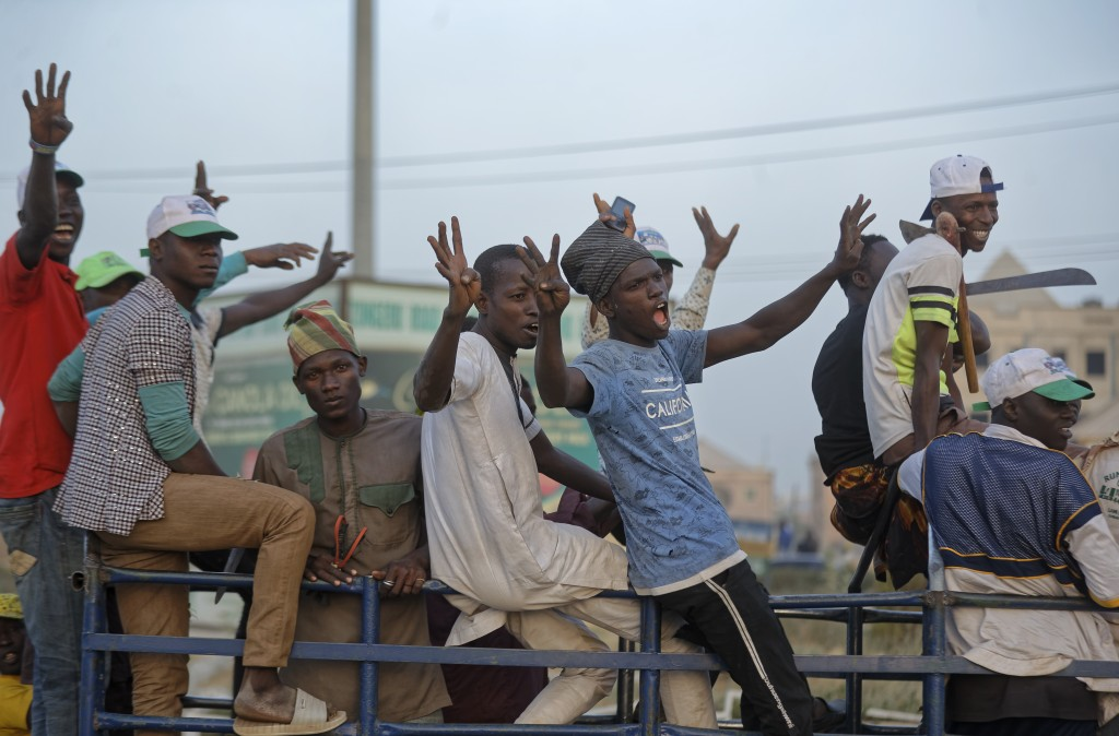 Youth cheer as they ride on the back of a truck returning from a rally of the ruling All Progressives Congress party, near the offices of the Independ...