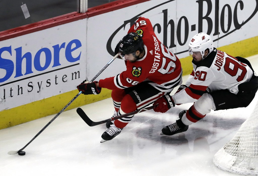 Chicago Blackhawks defenseman Erik Gustafsson, left, controls the puck against New Jersey Devils left wing Marcus Johansson during the second period o...