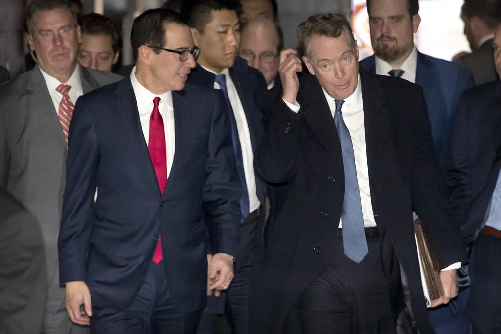 U.S. Treasury Secretary Steven Mnuchin, left, and U.S. Trade Representative Robert Lighthizer walk together as they leave their hotel in Beijing, Frid...
