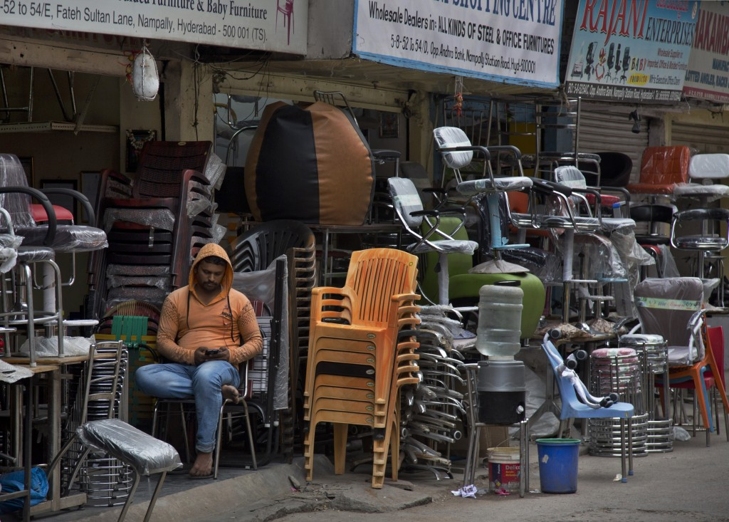 In this Dec. 17, 2018, photo, a salesman checks his mobile phone as he waits for customers at the Nampally furniture market in Hyderabad, India. Such ...